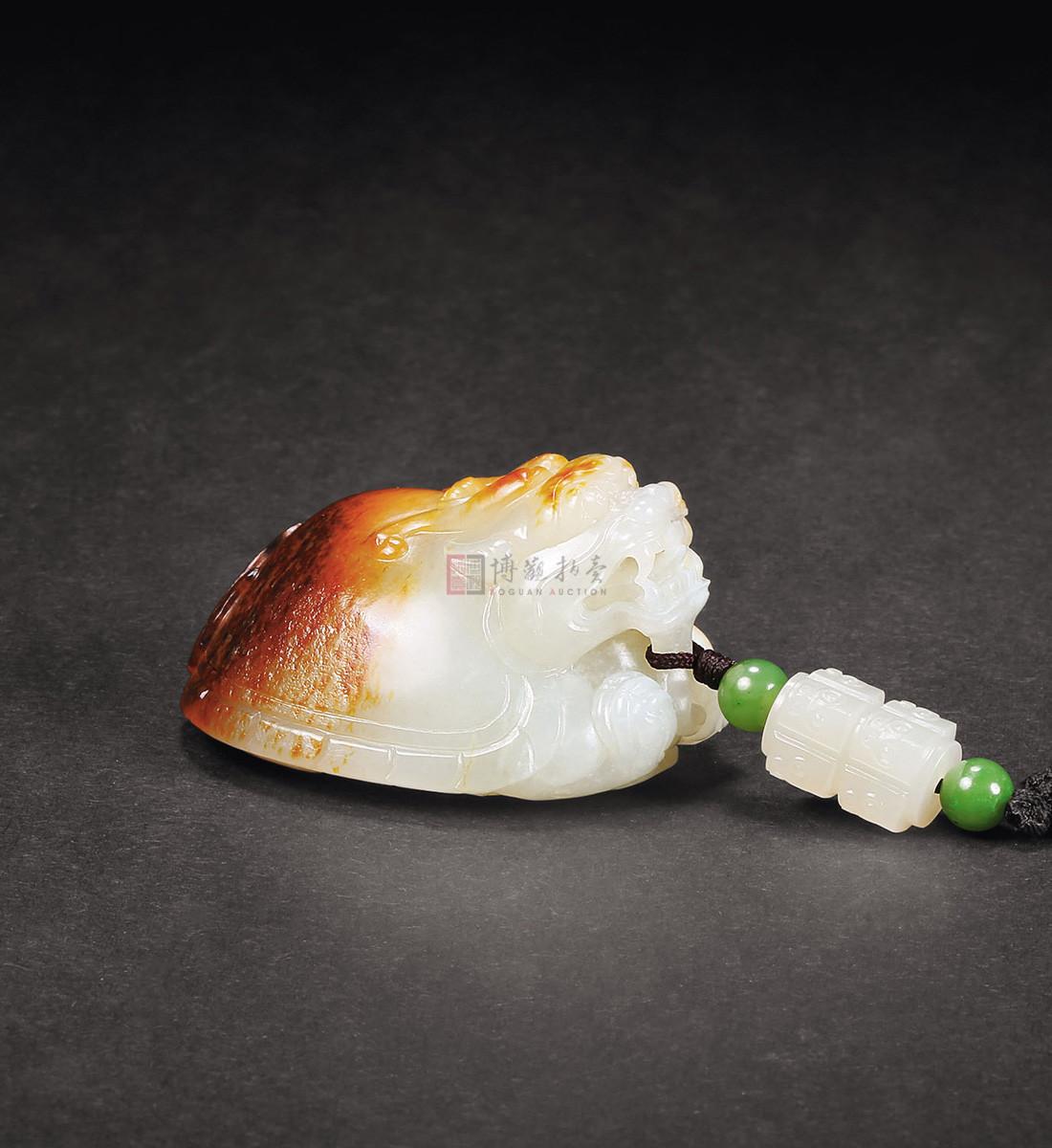 这件作品的设计较为巧妙,利用沁入玉料之中的黄褐色,整体设计为一只龙龟,点点褐色犹若龟壳之斑点,具厚重老气之感。范佰成,海派玉雕名家,江苏省徐州市人,2003年在上海创办石道居个人玉雕工作室,擅长动物、花鸟、人物及仿古件玉雕的设计与雕刻。